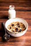 Breakfast super bowl of homemade granola or muesli with oat flakes, black currant, black raspberry and peanuts on a wooden table,. Selective focus. Served with royalty free stock photography
