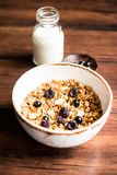 Breakfast super bowl of homemade granola or muesli with oat flakes, black currant, black raspberry and peanuts on a wooden table,. Selective focus. Served with stock image