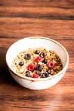 Breakfast super bowl of homemade granola or muesli with oat flakes, black currant, black raspberry and peanuts on a wooden table,. Selective focus. Served with royalty free stock photo