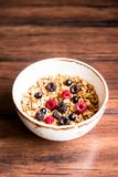 Breakfast super bowl of homemade granola or muesli with oat flakes, black currant, black raspberry and peanuts on a wooden table,. Selective focus. Served with Stock Photos