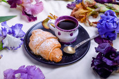 Breakfast with sweet croissants and coffee on black plate surrounded with iris flowers in bed. Good morning concept. Selective foc Stock Image