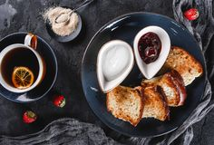 Breakfast with sweet homemade buns on plate over dark background, yogurt, strawberry jam, a cup of tea. Bakery, pastry, dessert,. Top view stock photos