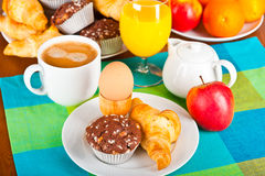 Breakfast table. Table set up for breakfast: coffee, egg, pastry, fruits Royalty Free Stock Photo