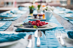 Breakfast table. Dining table set for breakfast with a plate of fresh fruit Royalty Free Stock Image