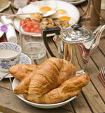 Breakfast Table. Continental breakfast with croissants and silver tea pot Royalty Free Stock Images