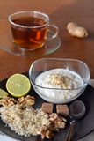 Breakfast table arrangement with jogurt, lemon, ground walnut and tea cup. Breakfast table arrangement with jogurt,cup of tea, lemon and ground walnut stock photos