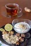 Breakfast table arrangement with jogurt, lemon, ground walnut and tea cup. Breakfast table arrangement with jogurt,cup of tea, lemon and ground walnut stock photography