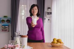 Breakfast table with Asian Elderly woman hold glass of milk at home stock images