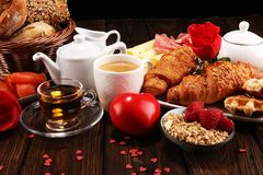 Breakfast on table with bread buns, croissants, coffe and juice on valentines day stock photography