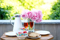 Breakfast table with bread, frest vegetables and berries, coffee and champagne served on balkony or hotel on summer