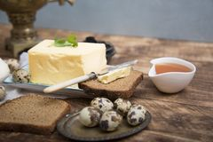 Breakfast table with bread slice, butter, black caviar, milk and honey. On wooden table Royalty Free Stock Photo