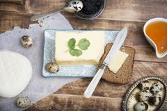 Breakfast table with bread slice, butter, black caviar, milk and honey. On wooden table Stock Photo