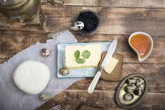 Breakfast table with bread slice, butter, black caviar, milk and honey. On wooden table Stock Image