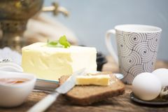 Breakfast table with bread slice, butter, black caviar, milk and honey. On wooden table Royalty Free Stock Photos