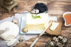 Breakfast table with bread slice, butter, black caviar, milk and honey. On wooden table Stock Photography