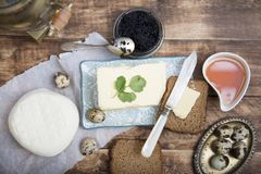 Breakfast table with bread slice, butter, black caviar, milk and honey. On wooden table Stock Images