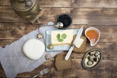 Breakfast table with bread slice, butter, black caviar, milk and honey. On wooden table Royalty Free Stock Images