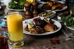 Breakfast table. Luxury and rich foods like orange juices. Cakes and also some desserts royalty free stock image