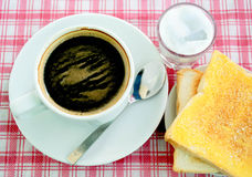 Breakfast table with coffee and toast with butter and sugar. One cup of black coffee, bread and butter plates, sprinkle with sugar, eat in the morning before Stock Image