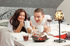 Breakfast on a table with couple lying Stock Image