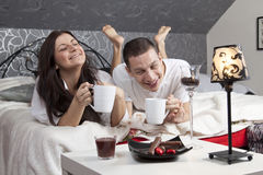 Breakfast on a table with couple lying Royalty Free Stock Image
