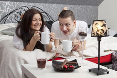 Breakfast on a table with couple lying Stock Images