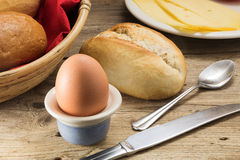 Breakfast table with egg, cheese, bread rolls, a basket with re Royalty Free Stock Photos