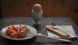 Breakfast on the table. Egg in a crumpled, sausage with tomatoes and white bread Royalty Free Stock Image
