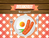 Breakfast table. Fried egg, sausages on a plate, fork and knife. Red checkered tablecloth on wooden table Royalty Free Stock Images