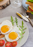 Breakfast table with fried eggs, bacon, cherry tomatoes, sanwiches royalty free stock photography
