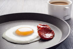 Breakfast on the table. Fried eggs with fried sausages salami and dill. Royalty Free Stock Image