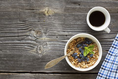 Breakfast table with granola, coffee and fresh berries. Healthy breakfast. A cup with homemade granola, a cup of fresh black coffee on a simple wooden background Stock Photography