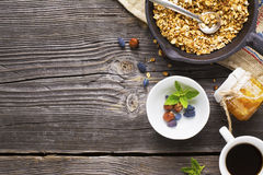 Breakfast table with granola, coffee and fresh berries. Healthy breakfast. A cup with homemade granola, a cup of fresh black coffee on a simple wooden background Stock Photo