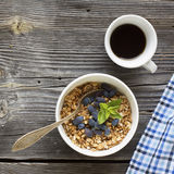 Breakfast table with granola, coffee and fresh berries. Healthy breakfast. A cup with homemade granola, a cup of fresh black coffee on a simple wooden background Stock Images