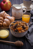 Breakfast table with granola, croissants, apple, coffee, juice Stock Photos