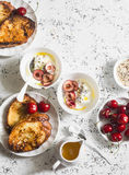 Breakfast table. Greek yogurt with cherries and honey and caramel french toast on white table, top view. Flat lay. Stock Images