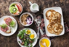 Breakfast table - greek yogurt with whole grain cereals and berry sauce, pancakes, arugula, cherry tomatoes, boiled eggs salad, ki. Wi, apples fruit, salami and Royalty Free Stock Image