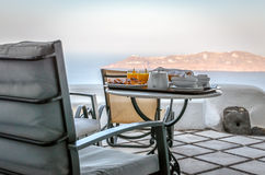 Breakfast table with juice and meal on balcony at Santorini island Royalty Free Stock Photography