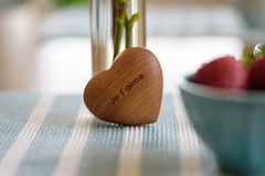 Closeup of wooden heart with the words je t`aime I love you in french. Breakfast table in morning light with closeup focus on wooden heart with the words I love Stock Photography