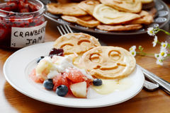 Breakfast table: pancakes, fruit salad, jam, yogurt Royalty Free Stock Image
