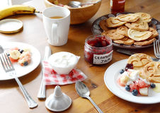 Breakfast table: pancakes, fruit salad, tea, yogurt Royalty Free Stock Images