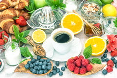 Breakfast table setting with coffee, croissants, granola, honey. Stock Photos