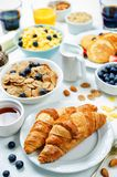 Breakfast table setting with flakes, juice, croissants, pancakes Royalty Free Stock Photography