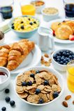 Breakfast table setting with flakes, juice, croissants, pancakes Stock Image