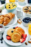 Breakfast table setting with flakes, juice, croissants, pancakes Stock Photos