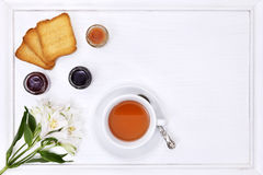 Breakfast table with tea, cup of tea, flower, jam and bread Stock Photo