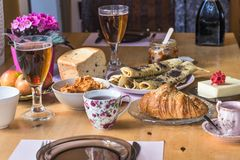 Breakfast table with tee,croissant,bread,pancakes,butter,honey,corn flakes and flowers Royalty Free Stock Image