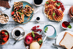Breakfast table with waffles. Yogurt, coffee and fresh fruits and berries on white wooden background, top view Stock Images