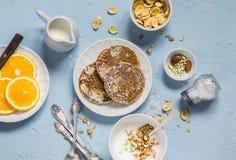 Breakfast table. Whole wheat pancakes, greek yogurt with homemade granola, orange slices, nuts, corn flakes Stock Images