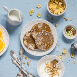 Breakfast table. Whole wheat pancakes, greek yogurt with homemade granola, orange slices, nuts, corn flakes Stock Image